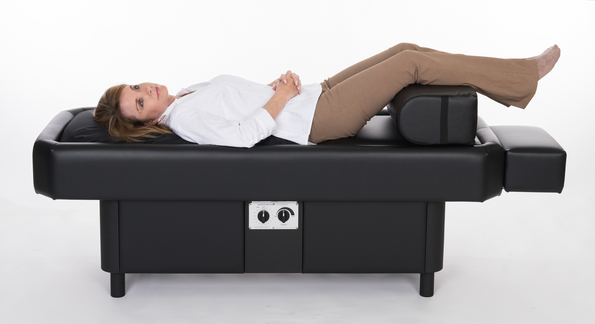lady on hydromassage table with leg bolster laying on the side