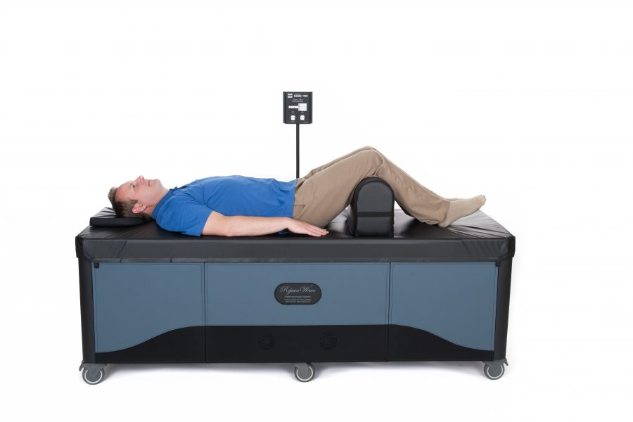 man on hydromassage table with knees raised on leg bolster
