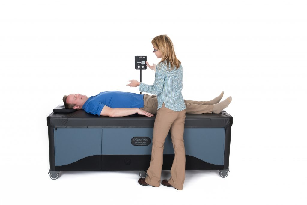 doctor putting patient on full body hydromassage table