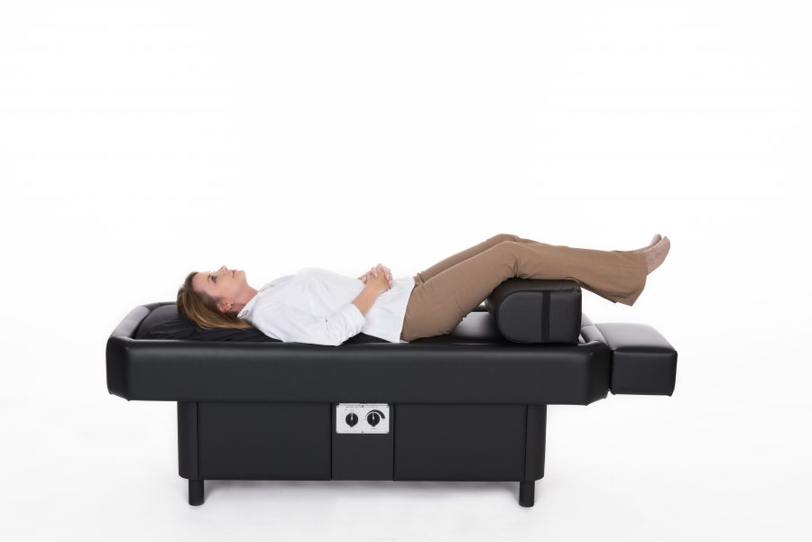 women on hydromassage table with leg bolster knees raised