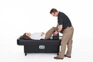 man adjusting leg bolster on hydromassage table
