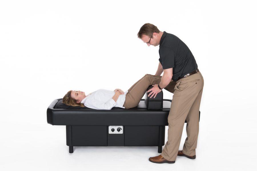 man adjust leg bolster on hydromassage table
