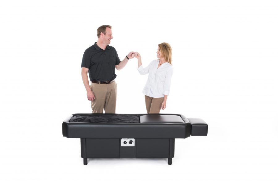 two happy people by black hydromassage table
